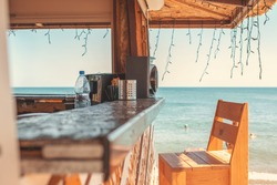 Sunny. An empty bar counter and an empty chair against the background of the beach and the sea. Vacation and summer