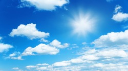Sunny background, blue sky with white clouds and sun as summer or spring natural background.