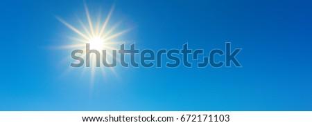 Sunny background, wonderful blue sky with bright sun - Shutterstock ID 672171103