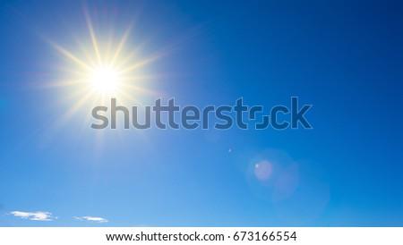 Sunny background, wonderful blue sky with bright sun - Shutterstock ID 673166554