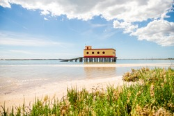 Sunny beach view of the historical life-guard building in Fuseta, Ria Formosa Natural park, Portugal