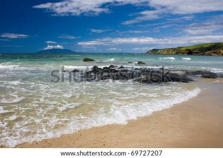 Sunny beach with a remote island on horizon - stock photo