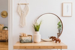 Sunny boho interiors of apartment with mirror, dressing table, furnitures, flowers, plants, rattan box, books, sculpture, macrame and design accessories. Stylish home decor of open space. Template.