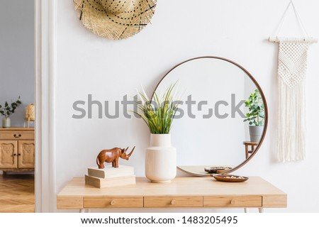 Sunny boho interiors of apartment with mirror, dressing table, furnitures, flowers, plants, rattan hat, sculpture, macrame and design accessories. Stylish home decor of open space. Template.