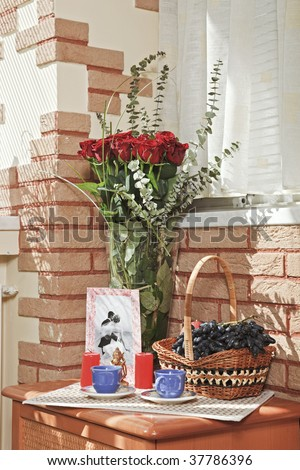 Sunny composition with rose bouquet and fruit basket on the bedside table