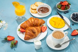 Sunny continental breakfast food on blue concrete table, with beautiful tropical plants shadows, coffee, croissants, orange juice, berries, mango, morning time holiday vacation concept
