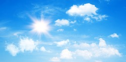 Sunny day background, blue sky with cumulus clouds and summer or spring sun as nature background.