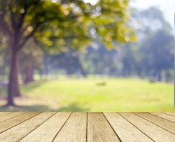 Sunny day background, Blur park, outside  landscape with bokeh light, Wood table and blur tree garden nature in sunny day background, Picnic table top for food and product display backdrop, mockup