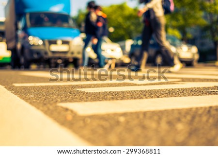 Sunny day in a city, pedestrians crossing the road. View from the level of asphalt, image in the yellow-blue toning