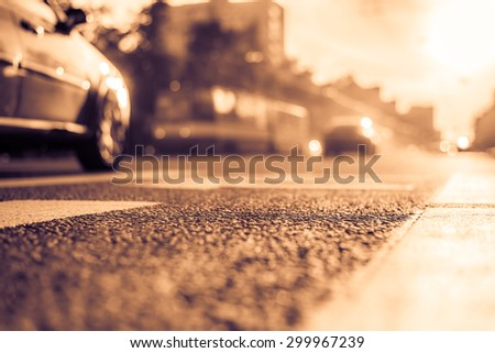 Sunny day in a city, smog on a city street, the view from the level of asphalt. Image in the yellow-purple toning