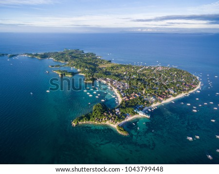 Sunny Day in Malapascua Island in Visayan Sea, One of Cebu Island. Sea water and Boats. Bounty Beach with Local Architecture