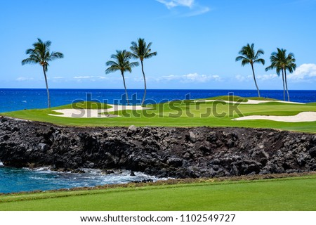 Sunny day on a tropical golf course fairway with the putting green in the distance surrounded by palm trees and sand traps, lava rock, blue pacific ocean, and blue sky and white clouds in background #1102549727