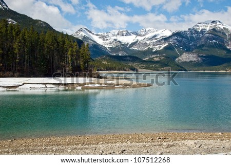 Sunny day on beautiful lake in Canadian Rockies with snow peaks on background
