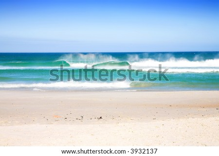 Sunny day on South African beach with big waves and clear blue sky