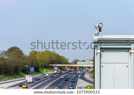 Sunny day view of UK motorway traffic with CCTV camera on foreground