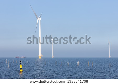 Sunny day with offshore wind turbines near Dutch coast with buoy and poles for fishing nets #1353341708