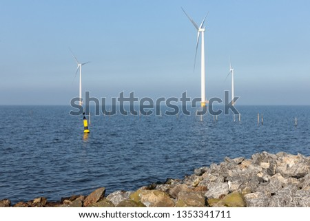 Sunny day with offshore wind turbines near Dutch coast with buoy and poles for fishing nets #1353341711