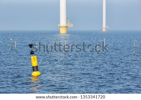Sunny day with offshore wind turbines near Dutch coast with buoy and poles for fishing nets #1353341720