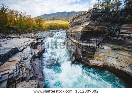 Sunny fall autumn view of Abisko National Park, Kiruna Municipality, Lapland, Norrbotten County, Sweden, with Abiskojokk river, road and Nuolja mountain, near border of Finland, Sweden and Norway Stock foto ©