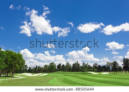 Sunny golf green with scattered clouds on a blue sky and forest