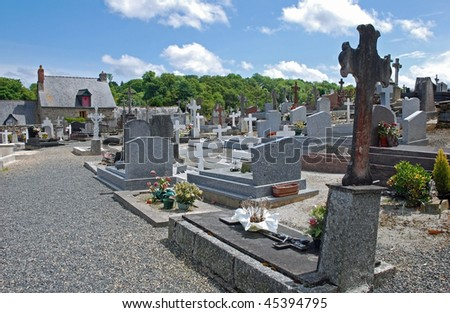 sunny graveyard with tombstones and building