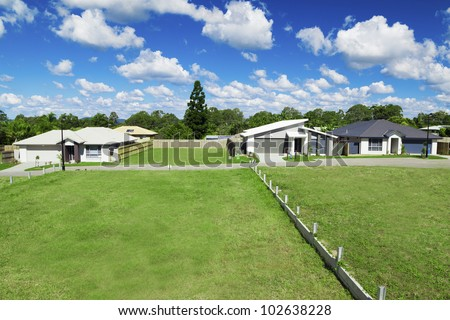 Sunny, green Australian housing development land with three newly built houses.