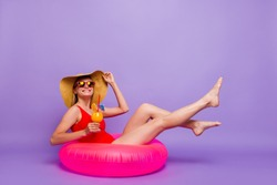 Sunny hot weather! Long-awaited trip journey tourism concept. Side profile full body length photo portrait of beautiful excited lady swimming in water lying lifebuoy isolated violet purple background