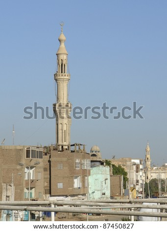 sunny illuminated architectural background with minaret around Esna, a city in Egypt (Africa)