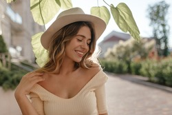 Sunny image of young stylish woman standing on street, in fashionable hat close-up. She has gentle smile and closed eyes. Nice neckline and bare shoulders.