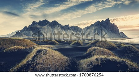 Sunny landscape of Iceland. Gorgeous view on Stokksnes cape and Vestrahorn Mountain with black sand with grass on foreground at summer. Iconic location for landscape photographers. Wonderful nature. Imagine de stoc ©