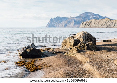 Sunny landscape of seaside shore with view of two stones, cape Chameleon, Kara-Dag mountains in south winter day. Black Sea, Koktebel, Crimea