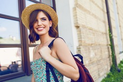 Sunny lifestyle fashion portrait of young stylish hipster woman walking on the street, wearing trendy outfit, straw hat, travel with backpack.