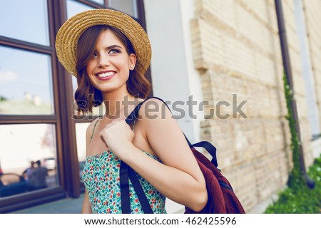 Shutterstock Sunny lifestyle fashion portrait of young stylish hipster woman walking on the street, wearing trendy outfit, straw hat, travel with backpack.