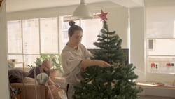 Sunny morning at home, caucasian young brunette woman in homewear putting garland decor on the fir tree for Christmas holidays. Man is sitting on the sofa watching phone. Light and warm atmosphere jpg