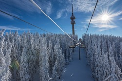 Sunny morning in the Rhodope Mountains, ski resort Pamporovo. Chair ski lift over pine trees. Snejanka TV tower in  background. Sports and recreation concept. Selective focus.