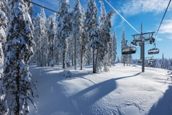 Sunny morning in the Rhodope Mountains, ski resort Pamporovo. Chair ski lift over pine trees. Snejanka TV tower in  background. Sports and recreation concept.Selective focus.