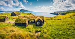 Sunny morning view of typical turf-top houses. Panoramic summer scene of outskirts of Torshavn city, capital of Faroe Islands, Kingdom of Denmark, Europe. Traveling concept background.
