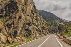 Sunny mountain landscape with Transfagarasan road meandering along high rocky steep cliffs in Fagaras mountains, Romania.