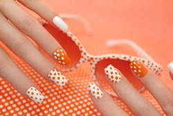 Sunny orange manicure with dots on the women's nails closeup.