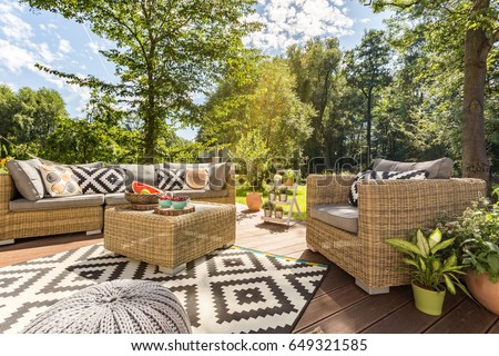 Sunny outdoor terrace with rattan furnitures in big garden