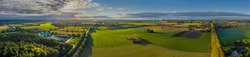 Sunny panorama of rural idyll with agricultural factory, fields, and long lime tree avenue in the countryside. Magical landscape in autumn.