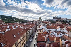 sunny panorama of the Czech capital, Prague, from tower with Prague Castle and red roofs houses