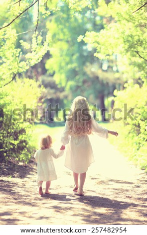 Sunny photo two little sisters holding hands walking barefoot in the forest on a summer day