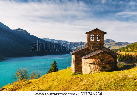 Sunny picturesque view of stone chapel on Roselend lake (Lac de Roselend) in France Alps (Auvergne-Rhone-Alpes). Landscape photography #1507746254