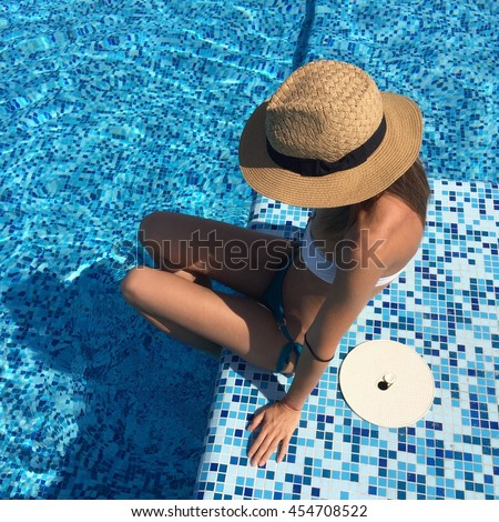 Sunny portrait beautiful girl on the top of rooftop in a pool.sexy girl in a hat,swimsuit,swimwear, skinny body,athletic figure,sunshine,relax time,beautiful tan