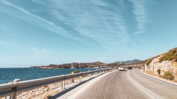 Sunny road driving on coastline of Aegean sea in Greece. Summer tourism travel. Scenic bright color graded day car drive vacation