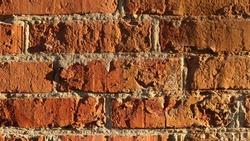 sunny shabby brick wall with uneven convex texture of knocked down blocks and light seams of putty, texture of vintage exterior surface reflective soft sunlight