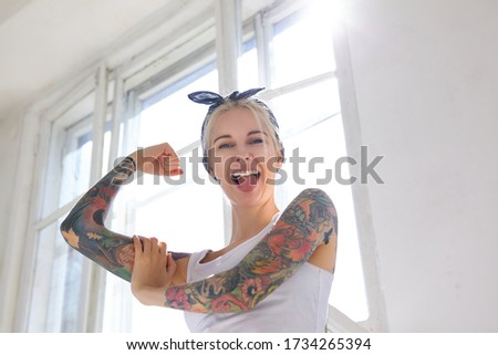 Sunny shot of joyful young pretty blonde woman with tattoos showing cherfully tongue to camera while demonstrating her strong biceps, posing in front of big window