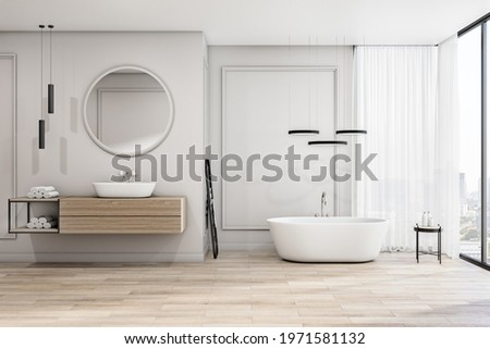Sunny spacious bathroom with white bath, stylish lamps, big round mirror over the sink, black decor details and city view from transparent wall. 3D rendering Сток-фото ©