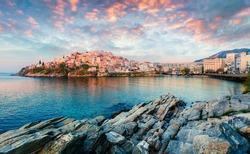 Sunny spring panorama of Aegean Sea. Colorful sunrise in Kavala city, the principal seaport of eastern Macedonia and the capital of Kavala regional unit. Greece, Europe.